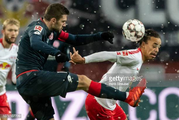 Yussuf Poulsen of RB Leipzig is challenged by Stefan Bell of Mainz 05 during the Bundesliga match between RB Leipzig and 1 FSV Mainz 05 at Red Bull...