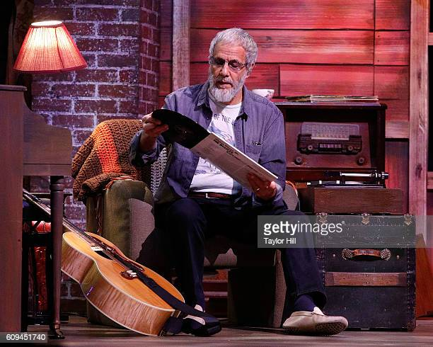 Yusuf Islam formerly known as Cat Stevens listens to a Beatles record onstage to demonstrate his influences during the 'A Cat's Attic' 50th...
