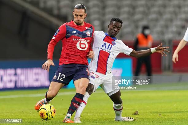Yusuf Yazici of Lille OSC is challenged by Idrissa Gueye of Paris SG during the Ligue 1 match between Lille OSC and Paris Saint-Germain at Stade...
