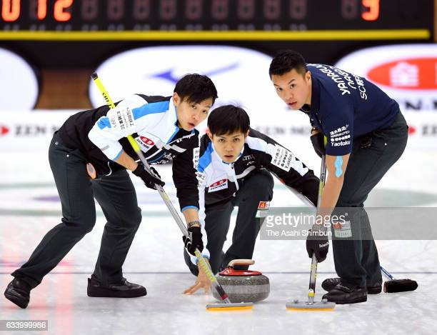 Yusuke Morozumi of SC Karuizawa deivers the stone while Kosuke Morozumi and Tsuyoshi Yamaguchi sweep in the 4th end in the Men's final during day...