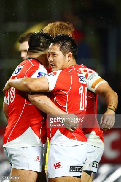 Yusuke Niwai of the Sunwolves celebrates with Takuma Asahara and Derek Carpenter after his try during the round 10 Super Rugby match between the...