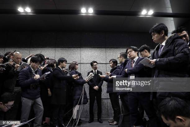 Yusuke Otsuka chief operating officer and cofounder of Coincheck Inc center speaks to members of the media at an entrance lobby of the building...