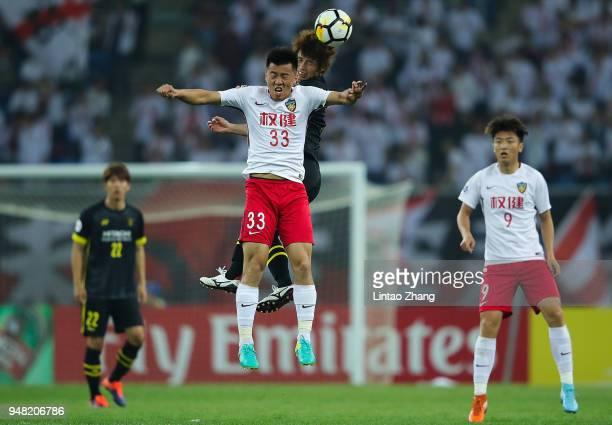 Yusuke Segawa of Kashiwa Reysol competes the ball with Chu Jinzhao of Tianjin Quanjian during the AFC Champions League Group E match between Tianjin...
