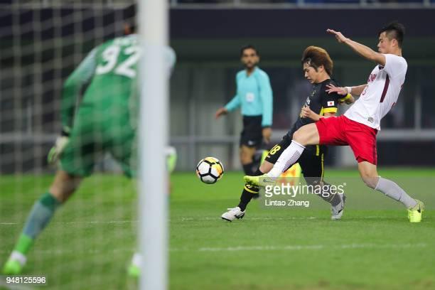 Yusuke Segawa of Kashiwa Reysol competes the ball with Pei Shuai of Tianjin Quanjian during the AFC Champions League Group E match between Tianjin...