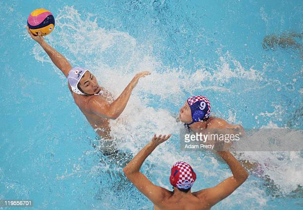 Yusuke Shimizu of Japan beats Josip Pavic and Sandro Sukno of Croatia in the Men's Water Polo first preliminary round match between Japan and Croatia...