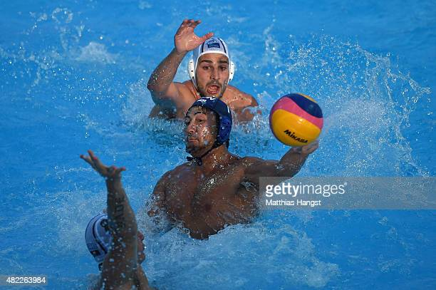Yusuke Shimizu of Japan throws the ball against Milos Cuk and Milan Aleksic of Serbia in the Men's Water Polo Preliminary Round Group D match between...