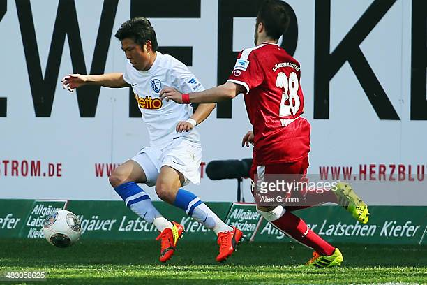 Yusuke Tasaka of Bochum is challenged by Kostas Fortounis of Kaiserslautern during the Second Bundesliga match between 1 FC Kaiserslautern and VfL...