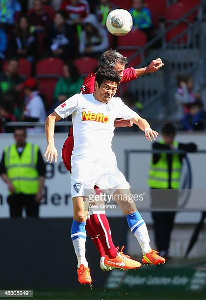 Yusuke Tasaka of Bochum jumps for a header with Marc Torrejon of Kaiserslautern during the Second Bundesliga match between 1 FC Kaiserslautern and...