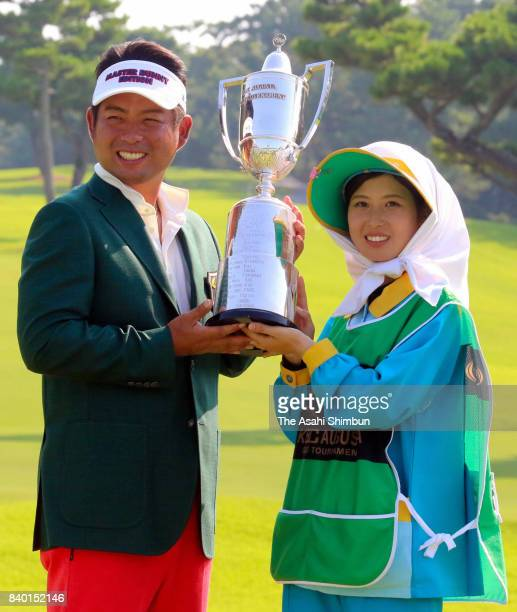 Yuta Ikeda of Japan and his caddie Arisa Yamazaki pose with the trophy after winning the RIZAP KBC Augusta at Keya Golf Club on August 27 2017 in...