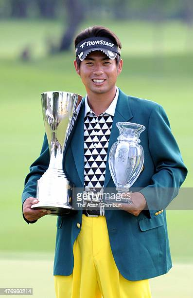 Yuta Ikeda of Japan poses for photographs with the trophies after the San Chlorella Classic at Otaru Country Club on July 31 2011 in Otaru Hokkaido...