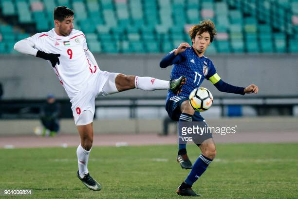 Yuta Kamiya of Japan and Oday Dabbagh of Palestine compete for the ball during the AFC U23 Championship Group B match between Japan and Palestine at...