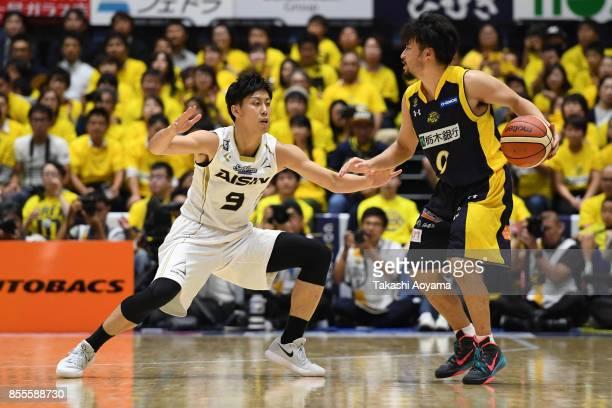 Yuta Tabuse of the Tochigi Brex handles the ball under pressure from Masaki Morikawa of the SeaHorse Mikawa during the BLeague game between Tochigi...