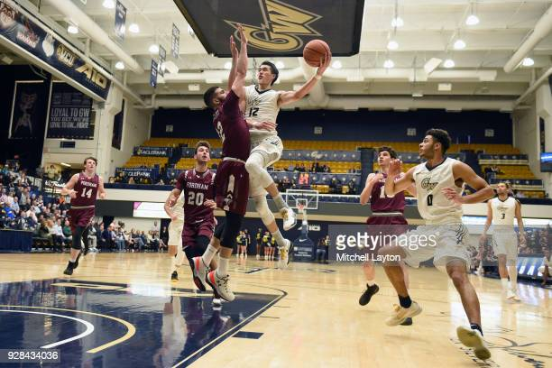 Yuta Watanabe of the George Washington Colonials drives to the basket over Joseph Chartouny of the Fordham Rams during a college basketball game at...