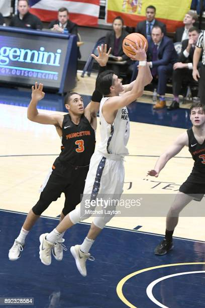 Yuta Watanabe of the George Washington Colonials drives tot he basket over Devin Cannady of the Princeton Tigers during a college basketball game at...