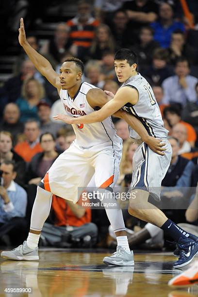 Yuta Watanabe of the George Washington Colonials puts pressure on Darion Atkins of the Virginia Cavaliers during a college basketball game at John...