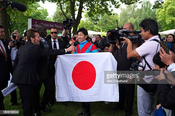 Yutaka Take with the Japanese flag at Longchamp racecourse on September 15 2013 in Paris France