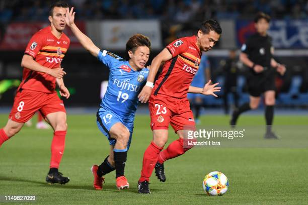 Yutaka Yoshida of Nagoya Grampus and Manabu Saito of Kawasaki Frontale compete for the ball during the J.League J1 match between Kawasaki Frontale...