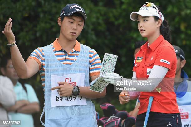 Yuting Seki of China speaks with her caddie before her tee shot on the 10th hole during the final round of the HokennoMadoguchi Ladies at the Fukuoka...