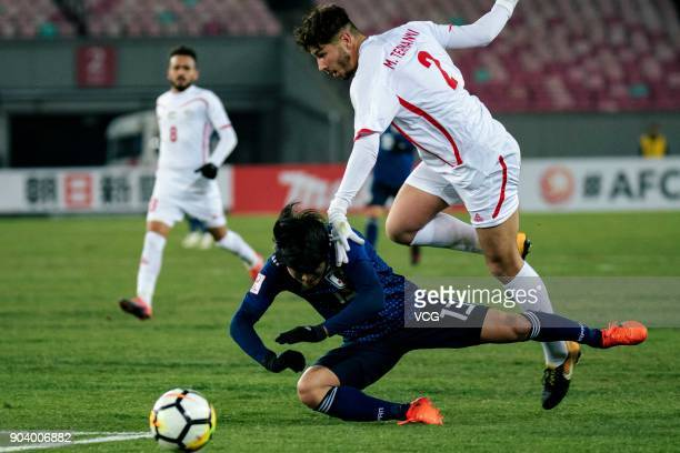 Yuto Iwasaki of Japan and Michel Termanini of Palestine compete for the ball during the AFC U23 Championship Group B match between Japan and...