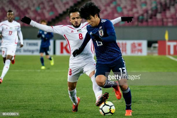 Yuto Iwasaki of Japan and Omar Sandouqa of Palestine compete for the ball during the AFC U23 Championship Group B match between Japan and Palestine...