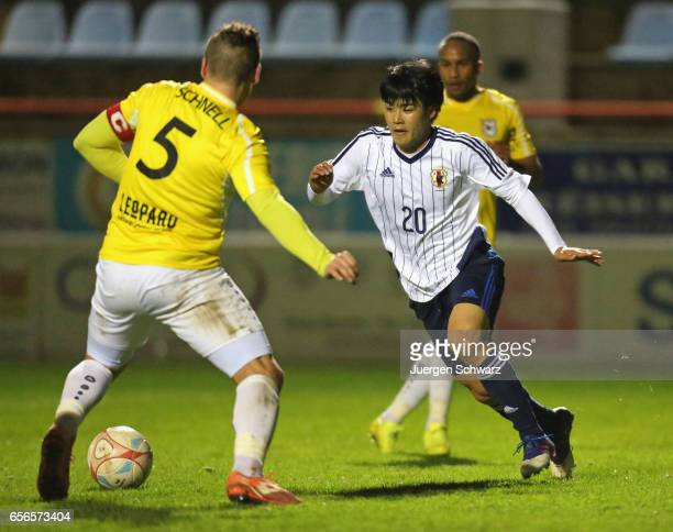 Yuto Iwasaki of Japan tackles Tom Schnell of F91 during a friendly soccer match between F91 Diddeleng and the Japan U20 team at Stade Jos Nosbaum on...