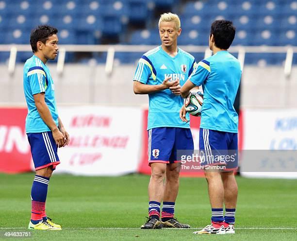 Yuto Nagatomo Keisuke Honda and Shinji Kagawa of Japan speak during an offcial training session ahead of the international friendly match between...