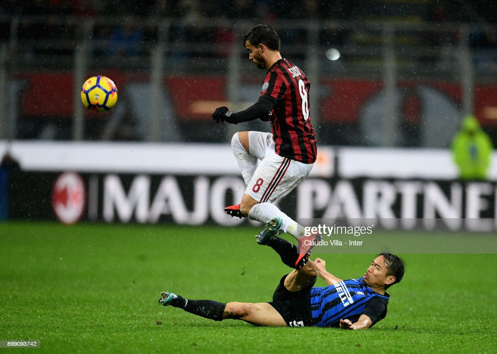 Yuto Nagatomo of FC Internazionale (R) and Suso of AC Milan compete for the ball during the TIM Cup match between AC Milan and FC Internazionale at Stadio Giuseppe Meazza on December 27, 2017 in Milan, Italy.