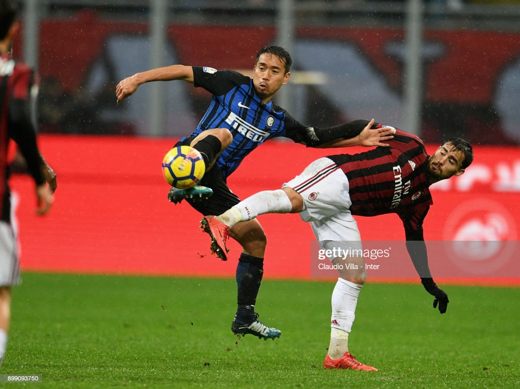 Yuto Nagatomo of FC Internazionale (L) and Suso of AC Milan compete for the ball during the TIM Cup match between AC Milan and FC Internazionale at Stadio Giuseppe Meazza on December 27, 2017 in Milan, Italy.