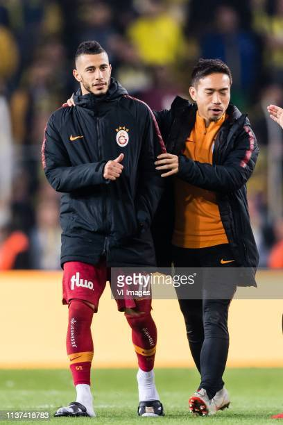Yuto Nagatomo of Galatasaray SK stops Younes Belhanda of Galatasaray SK to become unfriendly to Sadik Ciftpinar of Fenerbahce SK during the Turkish...