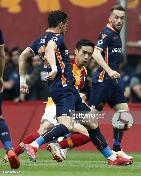 Yuto Nagatomo of Galatasaray vies for the ball with Irfan Can Kahveci of Basaksehir during the first half of Galatasaray's 21 win in Istanbul on May...