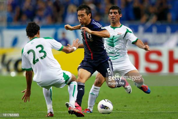 Yuto Nagatomo of Japan competes for the ball against Waleed Salim and Hammadi Ahmed of Iraq during the FIFA World Cup final qualifier match between...