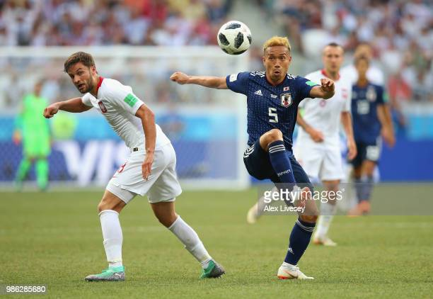 Yuto Nagatomo of Japan competes for the ball with Bartosz Bereszynski of Poland during the 2018 FIFA World Cup Russia group H match between Japan and...
