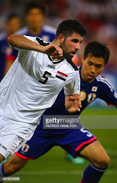 Yuto Nagatomo of Japan fights for the ball with Yaser Safa Kasim of Iraq during the first round Asian Cup football match between Japan and Iraq at...