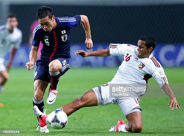 Yuto Nagatomo of Japan is challenged by Roberto Rosales of Venezuela during the international friendly match between Japan and Venezuela at Sapporo...