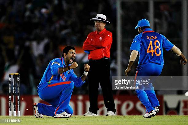 Yuvraj Singh of India celebrates with team mate Suresh Raina after taking the wicket of Younus Khan of Pakistan during the 2011 ICC World Cup second...