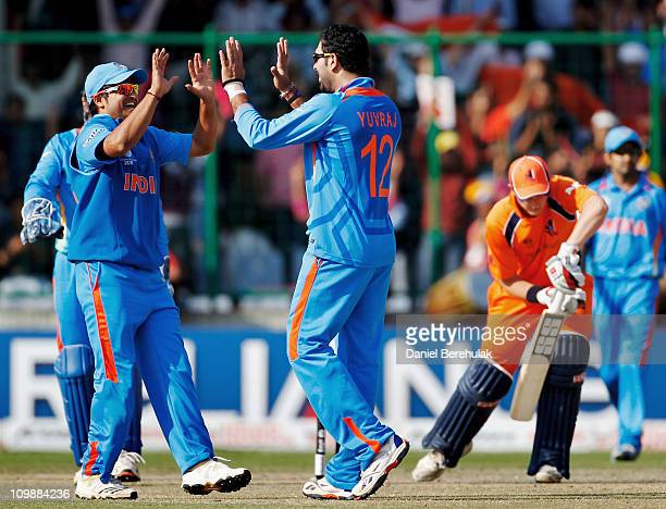 Yuvraj Singh of India celebrates with teammate Suresh Raina after taking the wicket of Wesley Barresi of the Netherlands during the 2011 ICC Cricket...