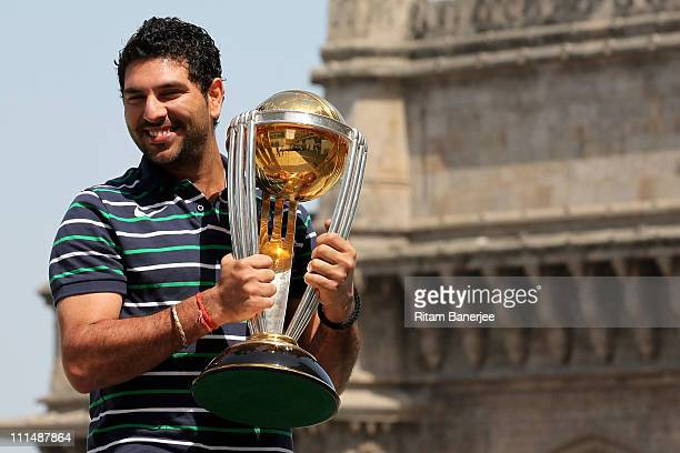 Yuvraj Singh of the Indian cricket team poses with the ICC Cricket World Cup Trophy with the Gateway of India in the backdrop during a photo call at...