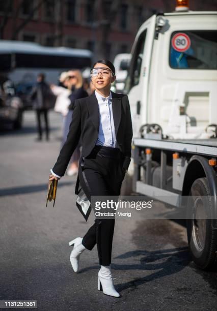 Yuwei Zhangzou is seen wearing black suit sunglasses golden clutch outside Armani on Day 2 Milan Fashion Week Autumn/Winter 2019/20 on February 21...