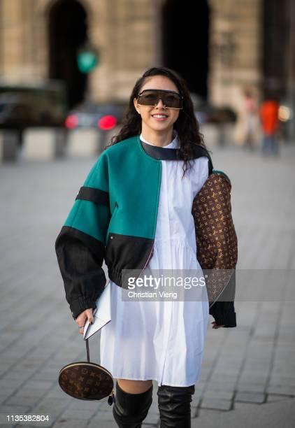 Yuwei Zhangzou is seen wearing jacket white dress overknees boots outside Louis Vuitton during Paris Fashion Week Womenswear Fall/Winter 2019/2020 on...