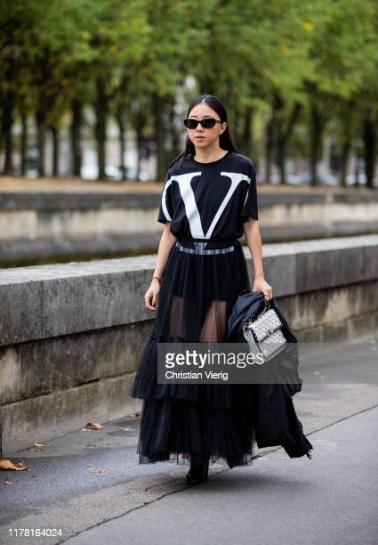 Yuwei Zhangzou seen wearing sheer skirt, logo top, white bag outside Valentino during Paris Fashion Week Womenswear Spring Summer 2020 on September...