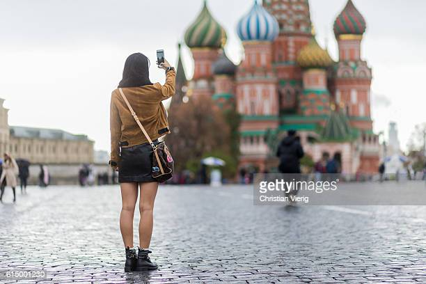 Yuwei Zhangzou taking tourist photos in front of Saint Basils Cathedral wearing a Louis Vuitton bag on October 15 2016 in Moscow Russia
