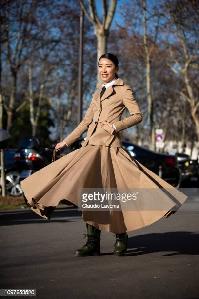Yuwei Zhangzou wearing a beige jacket with matching maxi skirt red bag and green boots is seen outside Christian Dior during Paris Fashion Week Haute...