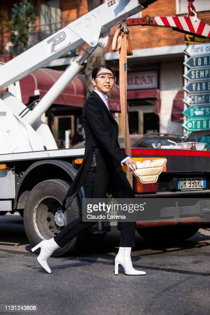 Yuwei Zhangzou wearing a black suit and white boots is seen outside Emporio Armani on Day 2 Milan Fashion Week Autumn/Winter 2019/20 on February 21...