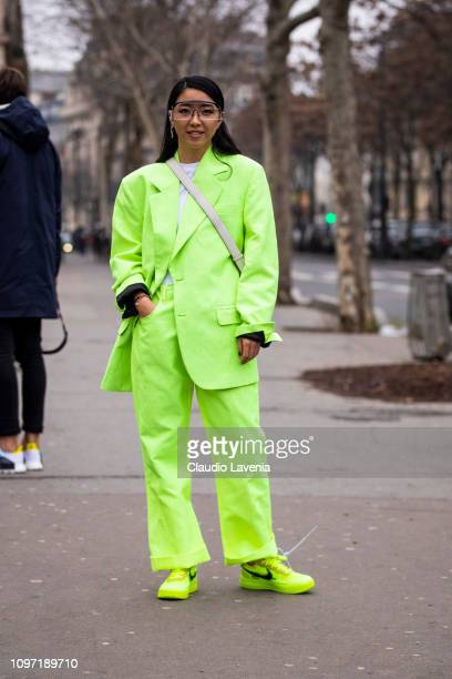 Yuwei Zhangzou wearing a neon green suit white tshirt neon green sneakers and grey bag is seen in the streets of Paris before the Acne Femme show on...
