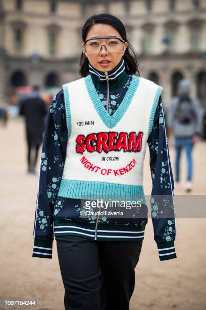 Yuwei Zhangzou wearing a printed sweatshirt black pants dark green boots and printed Kenzo vest is seen in the streets of Paris before the Kenzo show...