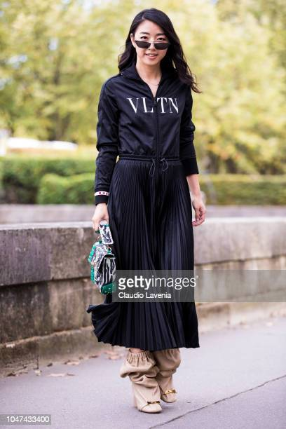Yuwei Zhangzou wearing a Valentino sweatshirt long black skirt beige boots and black and green bag is seen before the Valentino show on September 30...