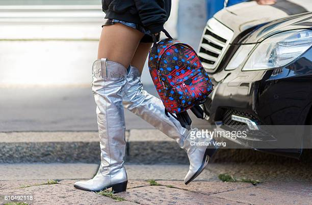 Yuwei Zhangzou wearing a Vetements hoody and Louis Vuitton backpack and silver overknees outside Ferragamo during Milan Fashion Week Spring/Summer...
