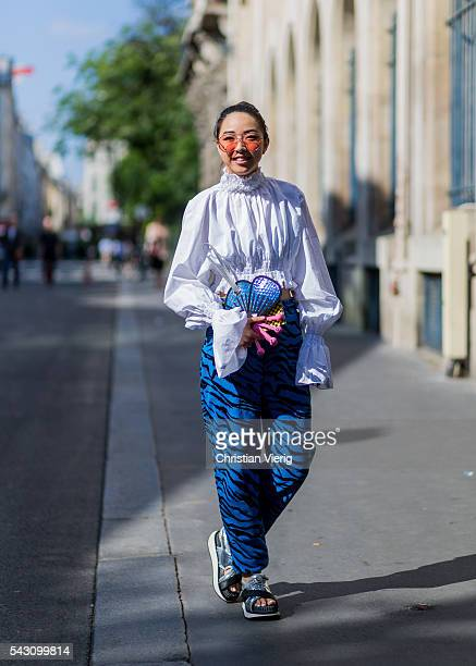 Yuwei Zhangzou wearing a white blouse Kenzo bag silver sandals and a blue pants outside during the Paris Fashion Week Menswear Spring/Summer 2017 on...