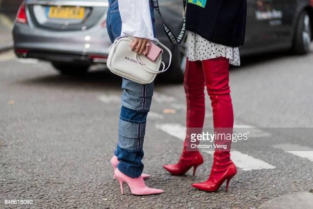 Yuwei Zhangzou wearing Balenciaga bag and Caroline Daur wearing knit red overknee boots outside Peter Pilotto during London Fashion Week September...