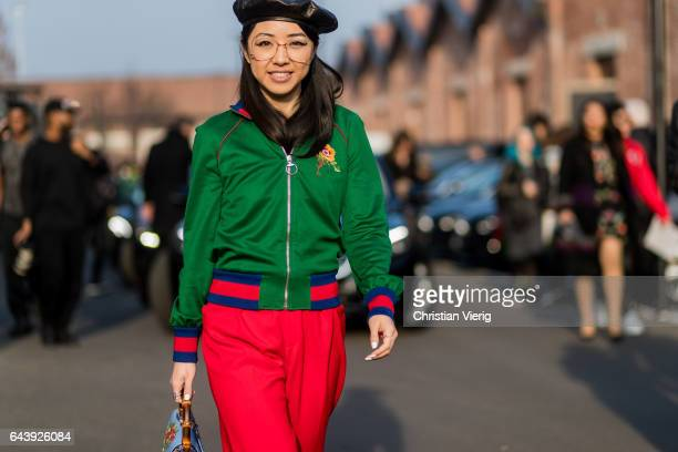 Yuwei Zhangzou wearing glasses black beret green Gucci jacket red pants blue Gucci bag outside Gucci on February 22 2017 in Milan Italy